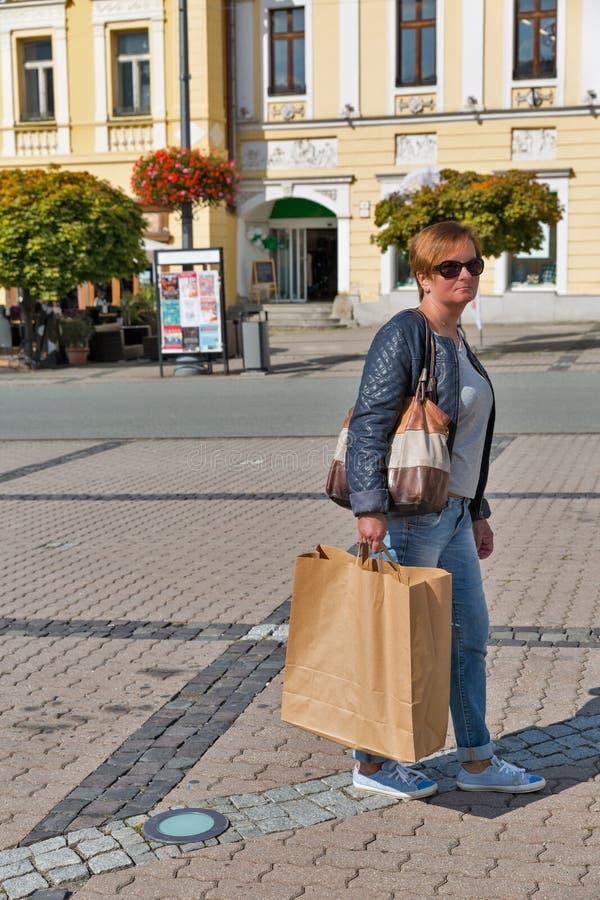 Le milieu a vieilli la femme heureuse avec des paniers marchant sur la rue images libres de droits