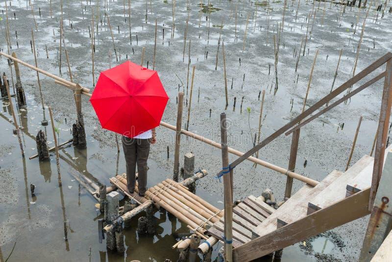 Le milieu a vieilli la femme se tenant sur un pont en bambou, sous un umbre rouge image libre de droits