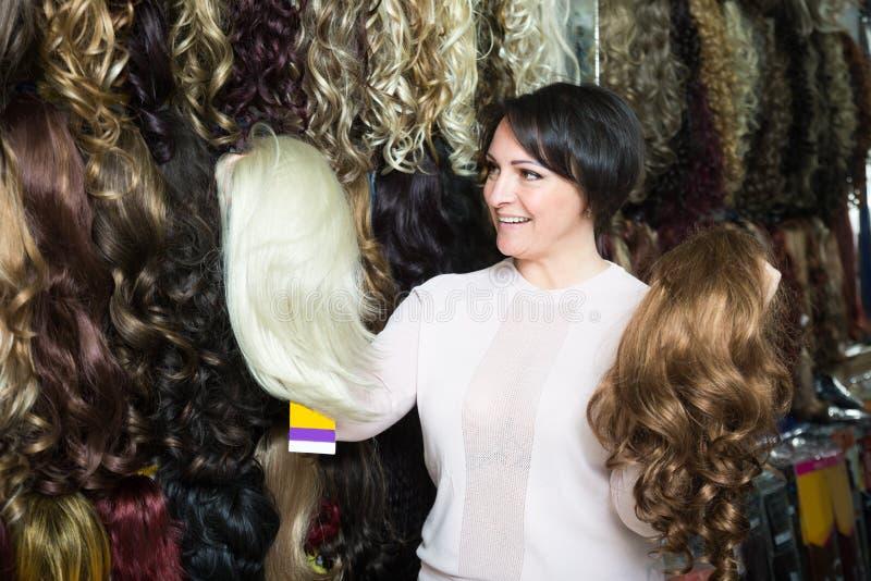 Le milieu a vieilli le client féminin sélectionnant la perruque naturelle de cheveux dans les cheveux s images stock