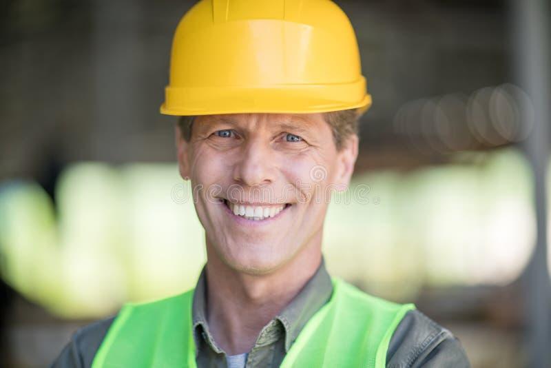 Le milieu a vieilli le constructeur dans le casque antichoc souriant à l'appareil-photo photo stock