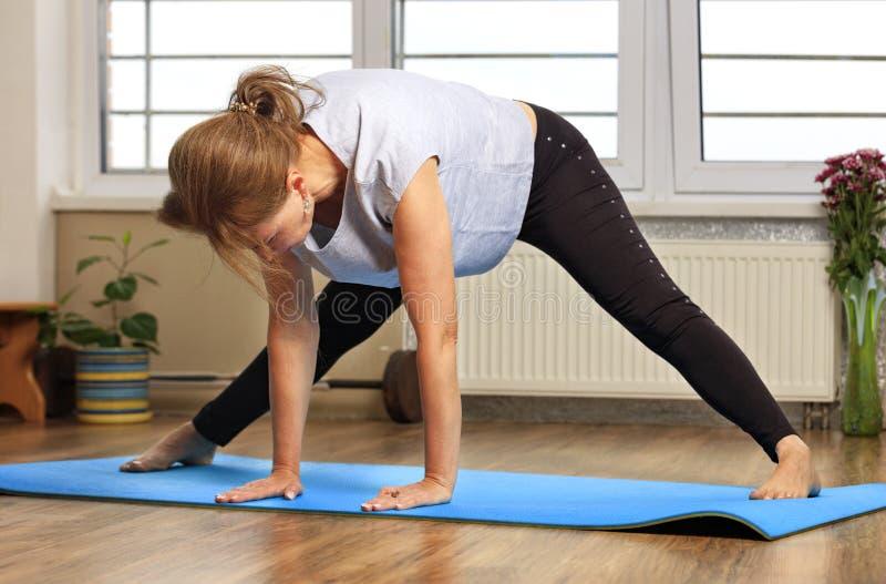 Le milieu a vieilli ou femme m?re faisant le yoga ? l'int?rieur image libre de droits