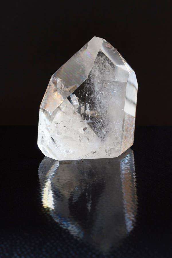 Le minerai de cristal de quartz montre ses propriétés optiques avec la réfraction légère sur le fond noir avec la réflexion photographie stock