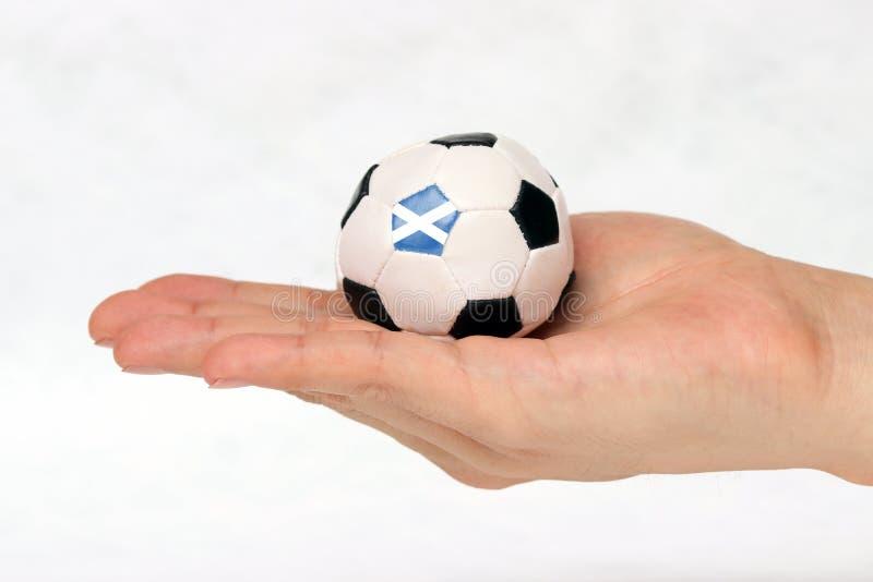 Le mini football à disposition et un point noir de football est drapeau de l'Ecosse sur le fond blanc photos libres de droits