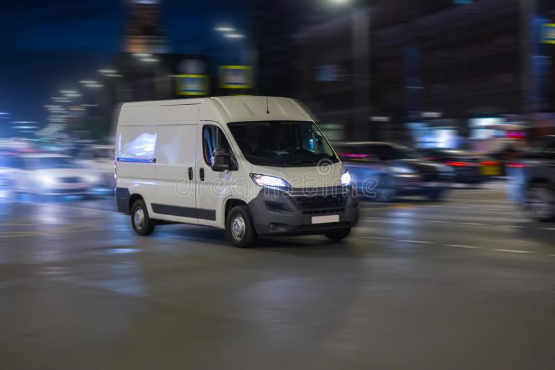 Le minibus se déplace la nuit le long de ville photo stock