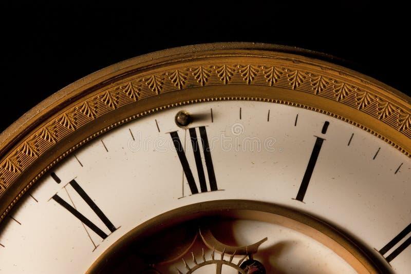 Le minuit frappe le foyer sur l'horloge de 12 o sur une vieille horloge image libre de droits