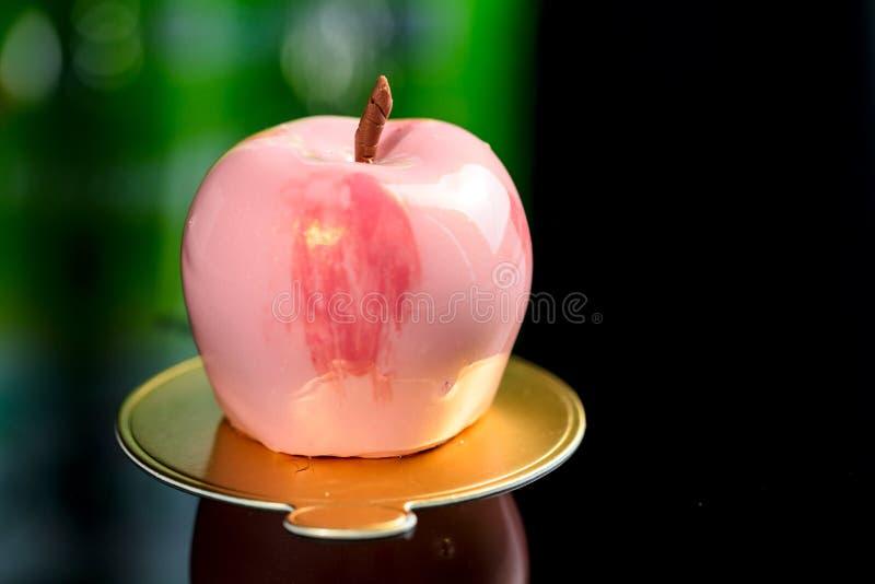 Le miroir rose à la mode a glacé le gâteau de mousse dans la forme de la pomme, sur le fond foncé photographie stock