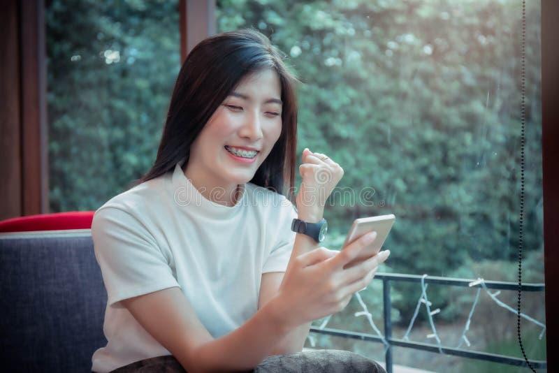 Le mobile se tenant de la belle fille d'Asiatique et avoir le t?l?phone portable de regard heureux d'?motion photographie stock libre de droits