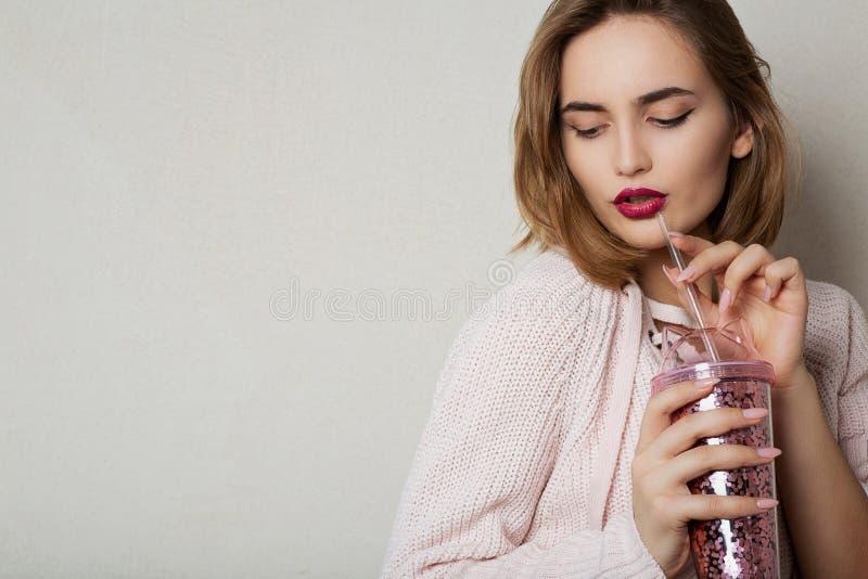 Le modèle à la mode de brune utilise le chandail rose, buvant le cocktail au studio L'espace pour le texte images libres de droits
