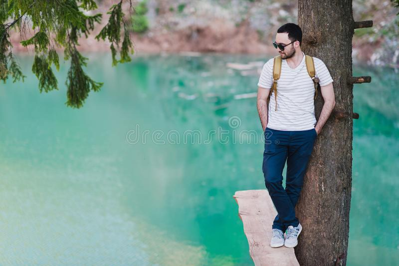 Le modèle barbu d'homme pose à côté d'un lac vert de l'eau photos libres de droits