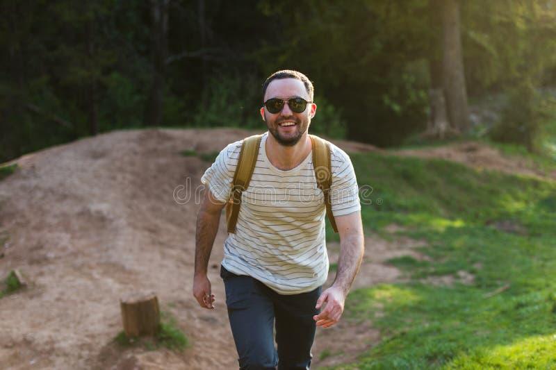 Le modèle barbu d'homme pose à côté d'un lac vert de l'eau image libre de droits