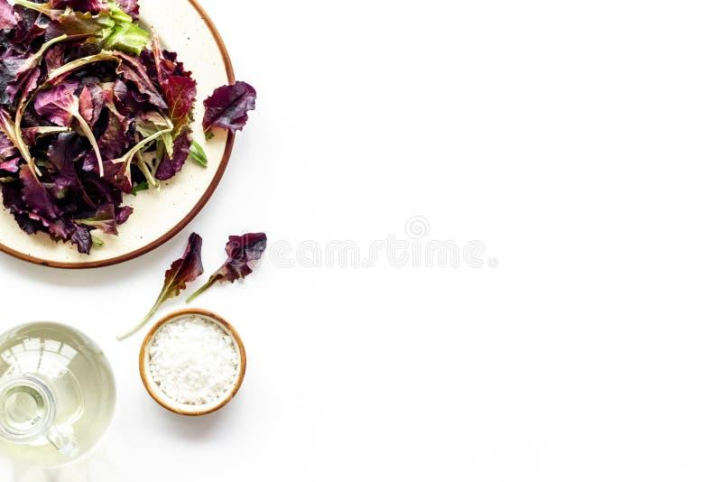 Le modèle d'aliment biologique avec des salades vertes et rouges mélangent et huilent l'espace blanc de vue supérieure de fond po photos stock