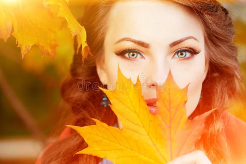Le modèle d'automne, lumineux composent femme sur le paysage de chute de fond images libres de droits