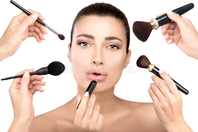 Le modèle de beauté avec des brosses de maquillage composent dedans le processus photos libres de droits
