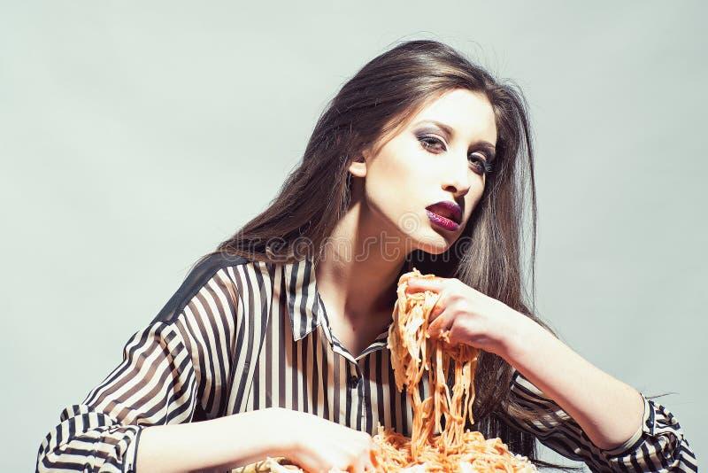 Le modèle de beauté avec le maquillage et les longs cheveux de brune dînent La femme sexy mangent des spaghetti avec des mains La photo libre de droits