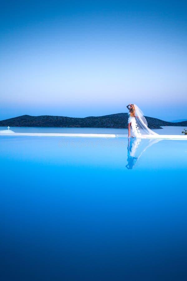 Le modèle femelle blond de belle jeune mariée dans la robe de mariage étonnante pose sur l'île de Santorini image libre de droits