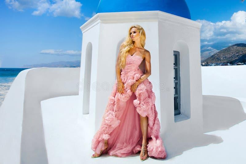 Le modèle femelle blond de belle jeune mariée dans la robe de mariage étonnante pose sur l'île de Santorini photos stock