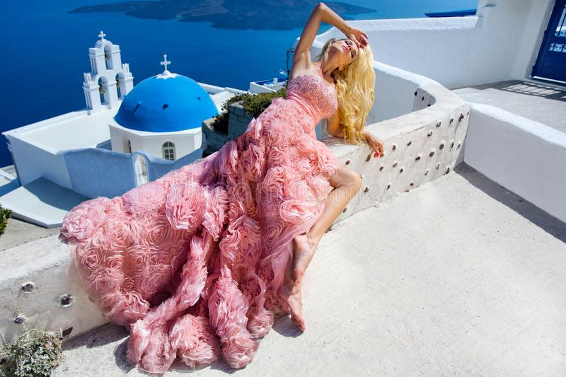 Le modèle femelle blond de belle jeune mariée dans la robe de mariage étonnante pose sur l'île de Santorini en Grèce photo libre de droits