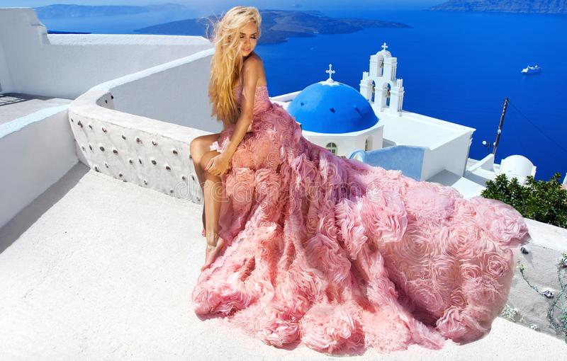 Le modèle femelle blond de belle jeune mariée dans la robe de mariage étonnante pose sur l'île de Santorini en Grèce photographie stock