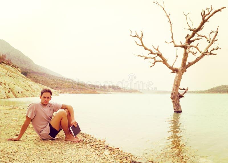 Le modèle masculin de hippie s'est reposé par un lac avec un livre photo libre de droits
