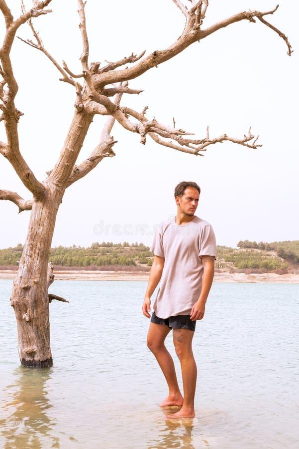 Le modèle masculin s'est tenu sous un arbre de mort dans un lac inondé photo libre de droits