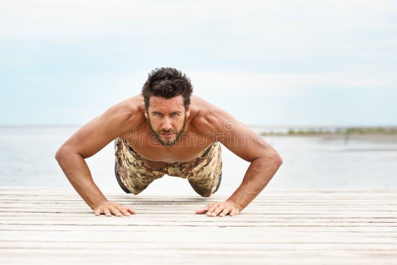 Le modèle masculin sans chemise convenable de forme physique soulèvent dedans l'exercice photographie stock