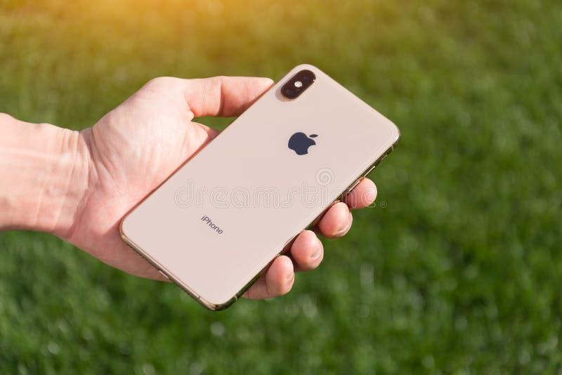 Le modèle maximum de smartphone d'or d'IPhone Xs par des ordinateurs Apple se ferment dans la main masculine sur le fond de l'her image libre de droits