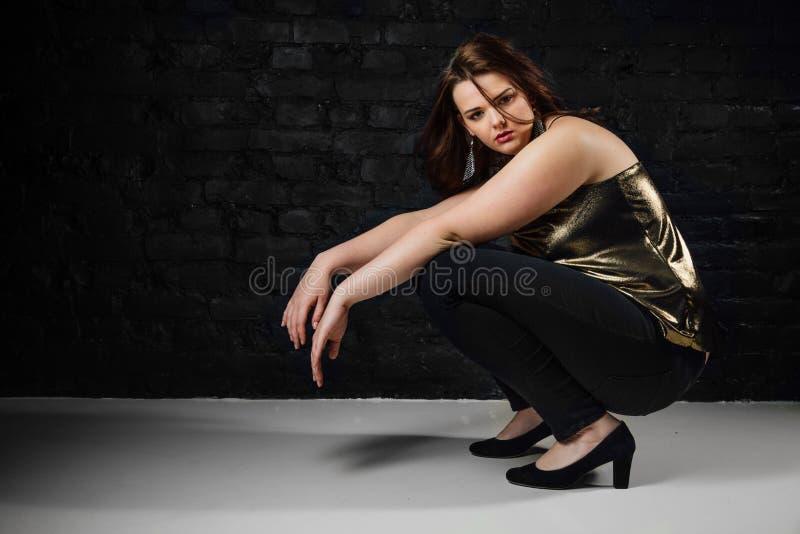 Le modèle plus de taille dans un chemisier d'or et les jeans noirs sur une brique tracent le fond photos libres de droits