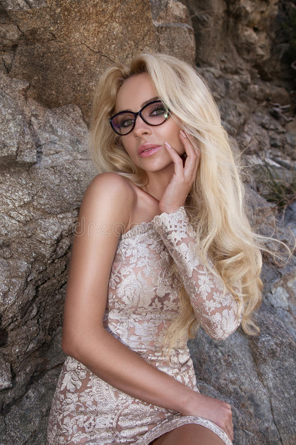 Le modèle sexy de jeune fille de femme de cheveux blonds dans des lunettes de soleil et l'or élégant s'habillent longtemps photos stock