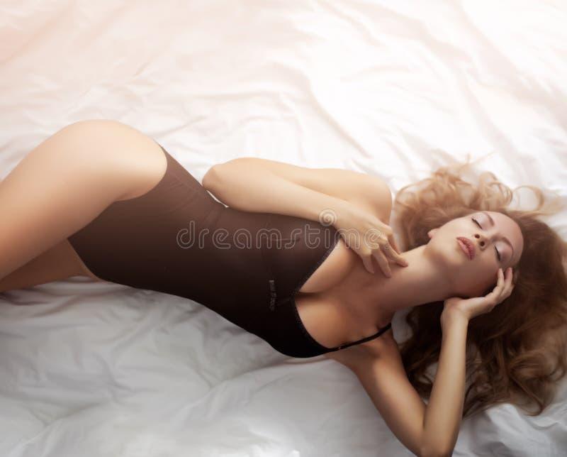 Le mod?le sexy magnifique utilisant la belle lingerie noire de corps se trouve sur le lit image libre de droits