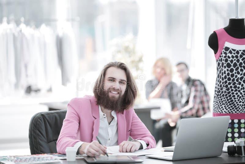 Le modeformgivaren på tabellen i en modern studio fotografering för bildbyråer