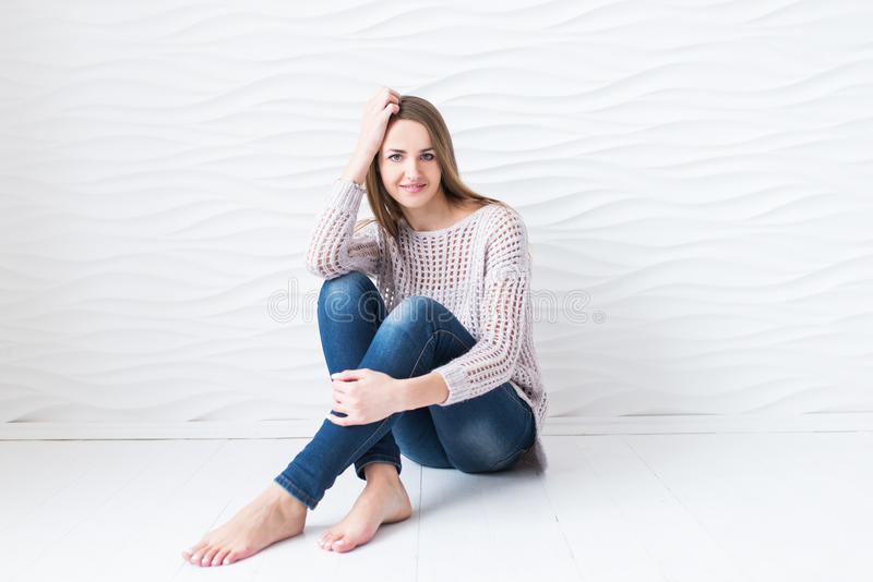 Le modellkvinnan med långt hår som ser kamerasammanträde på golvet på en vit bakgrund Hon är rädd royaltyfria bilder