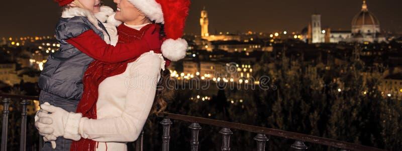 Le modern och barnet i julhattar, i Florence att omfamna arkivfoton