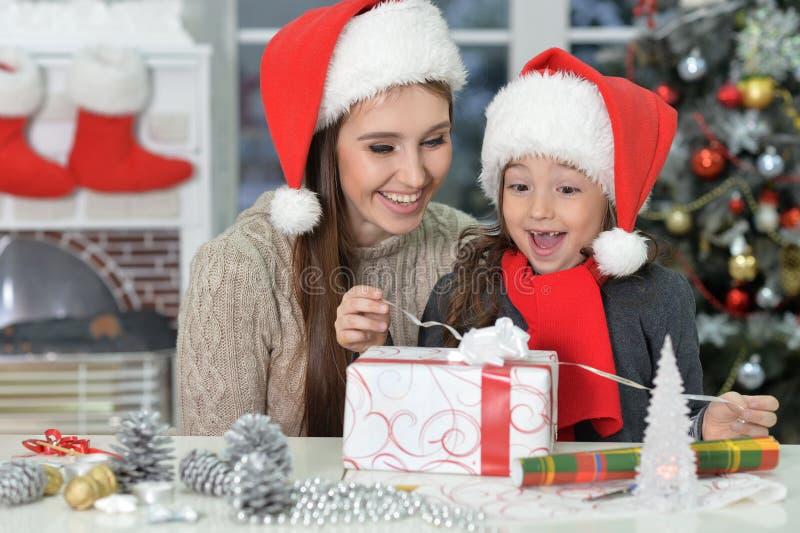 Le modern och den gulliga lilla dottern som hemma som firar jul bär jultomtenhattar arkivbilder