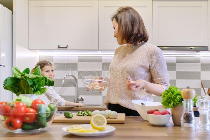 Le modern och dottern som tillsammans lagar mat i kökgrönsaksallad Sund hem- mat, kommunikationsf?r?lder och barn arkivfoto