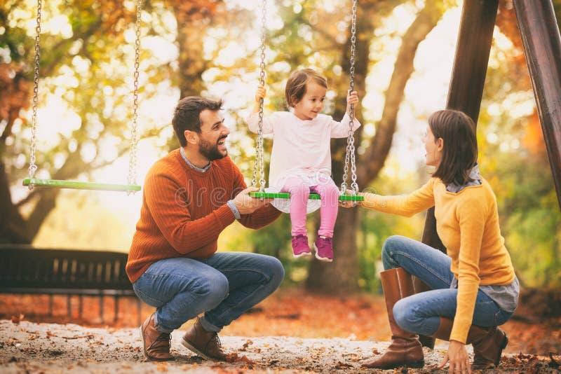 Le modern och f?r fader den sv?ngande parkerar barn p? royaltyfria foton