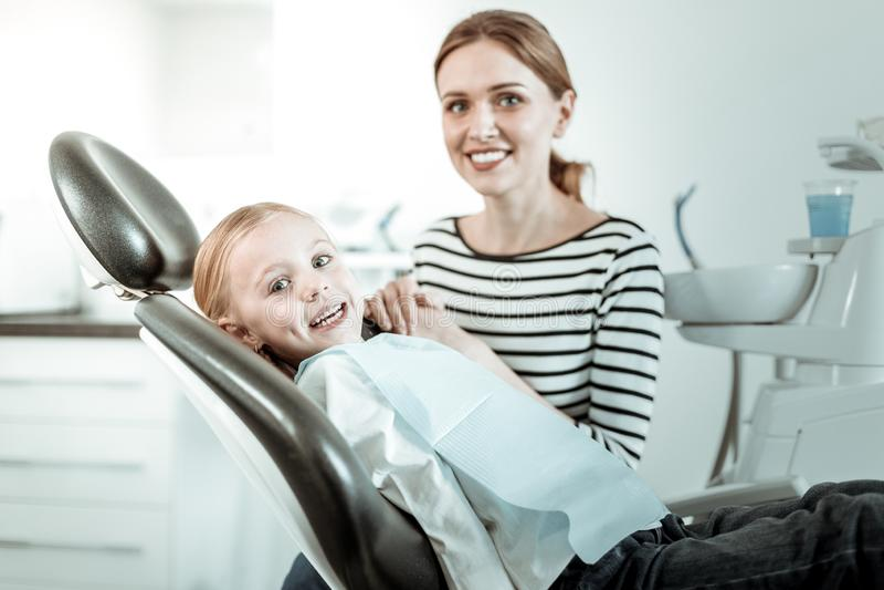 Le modern och hennes gladlynta dotter som har tandläkaretidsbeställning royaltyfria foton