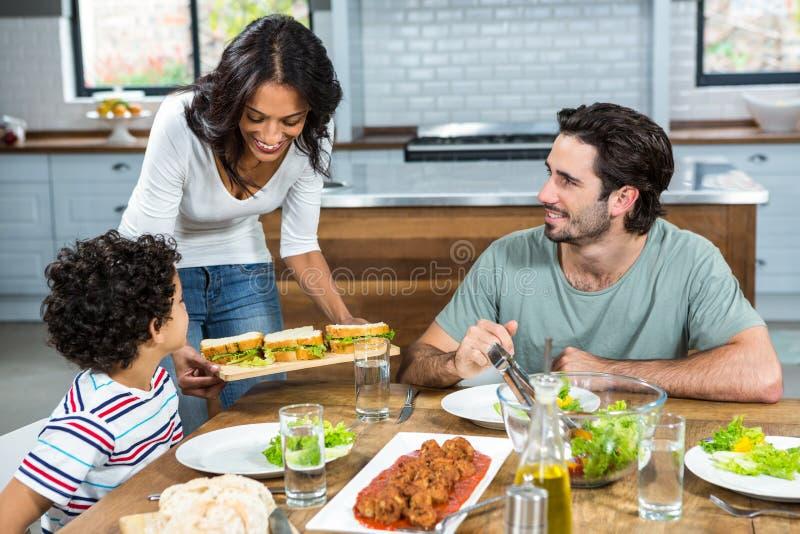 Le modern som ger smörgåsar till hennes son och make royaltyfri foto