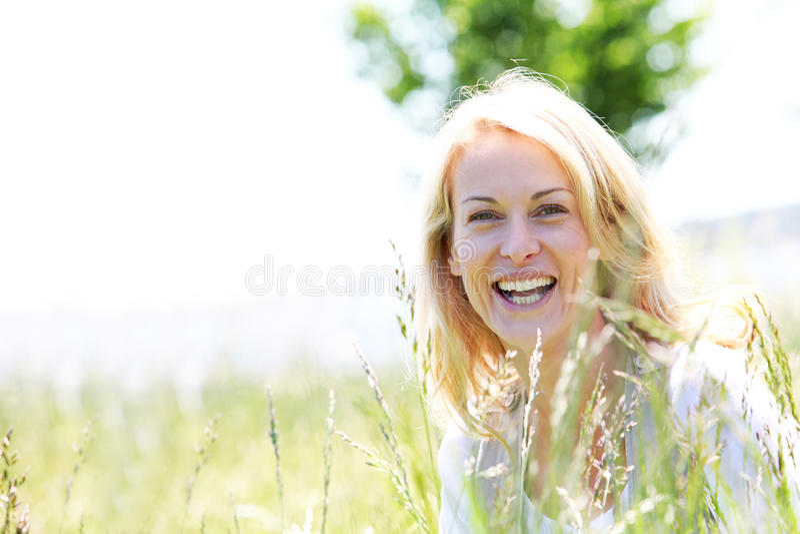 Le moget blont kvinnaanseende i äng royaltyfria bilder