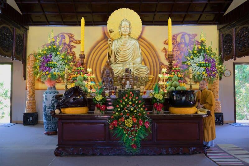 Le moine bouddhiste à un autel avec le Bouddha s'asseyant dans une de pagodas de Thien Vien Truc Lam Monastery Le Vietnam, Dalat photos stock