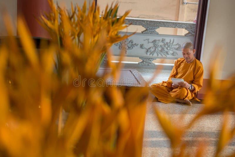 Le moine bouddhiste s'assied dans la lecture de porte de temple photographie stock libre de droits