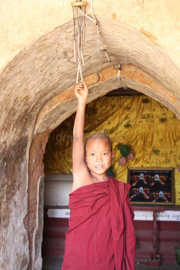 Le moine de novice sonne la cloche devant un temple, Bagan, Myanmar photos libres de droits