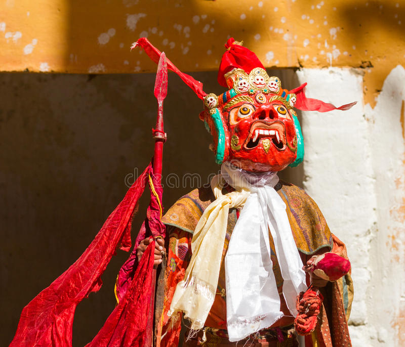 Le moine non identifié dans le masque avec la lance exécute la danse religieuse de mystère du bouddhisme tibétain pendant le fest images stock