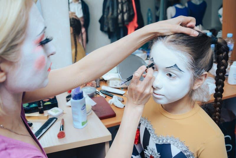 le moment de s'appliquer le maquillage de clown à une petite fille photo libre de droits