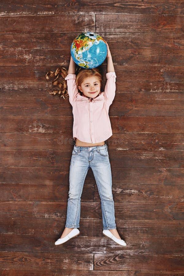 Le monde est le mien Globe de participation de fille, regardant la caméra et le sourire image libre de droits
