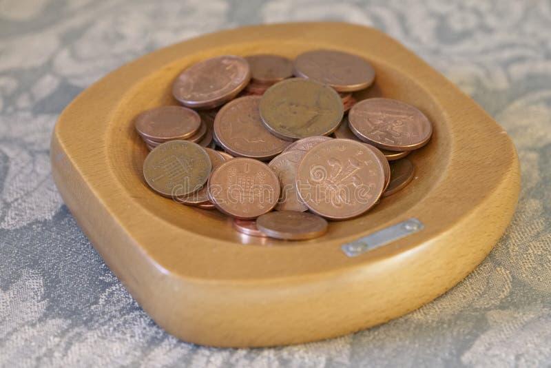 Le monete della raccolta ramano il risparmio di penny in ciotola di legno immagini stock