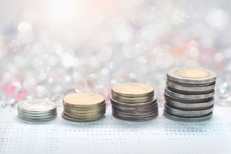 Le monete impilano davanti ai soldi di risparmio del libro contabile di conto bancario del concetto delle monete per la proprietà immagini stock