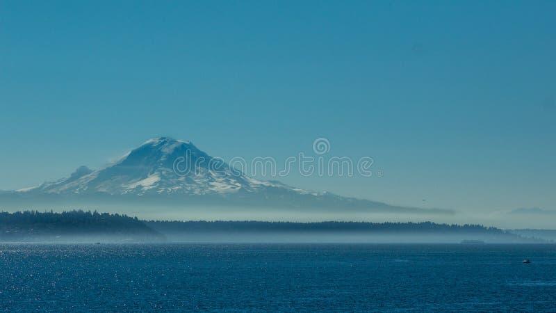 Le mont Rainier avec un saupoudrage de neige vu de l'eau avec un ciel bleu images libres de droits