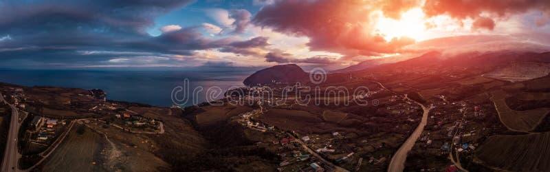 Le montagne della Crimea aeree abbelliscono il panorama al tramonto con le nuvole ed il mare drammatici Bello fondo di viaggio co fotografia stock