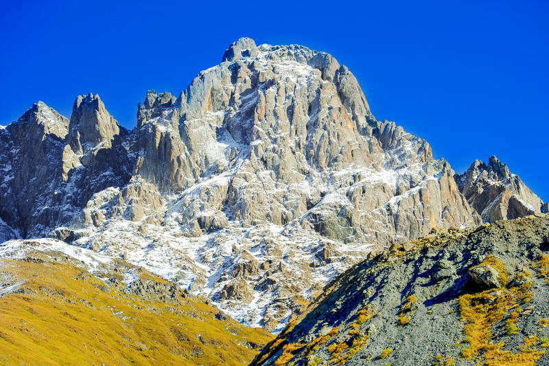 Le montagne di Caucaso di estate, l'erba verde sulle colline e la neve su Chiukhebi alzano villaggio Juta, Georgia fotografia stock