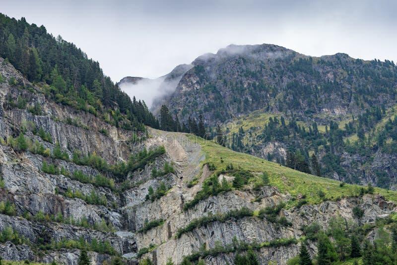 Le montagne, i picchi, il lago, il ghiaccio eterno e gli alberi abbelliscono fotografie stock libere da diritti